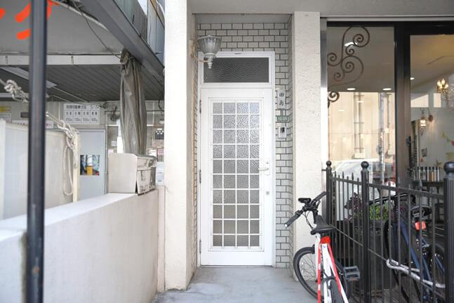 白いドアは営業時間中、基本常時明けておりますので、ドアを開け階段を上って2階へお進みください。 すぐ右手のドアが「スギタカメラ」です